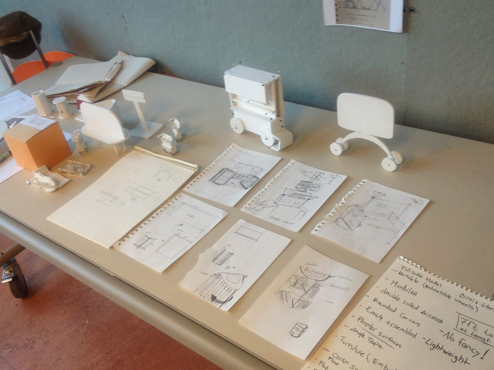 A table with several mockup sketches ordered together with foam core model mockups alongside the pages.