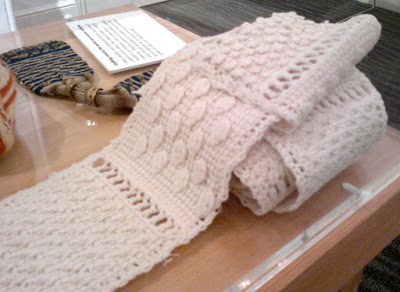 An off-white sampler scarf rolled up on the right hand side and laid out on the left. It is made up of squares separared by a row of filet openwork. Each square has a textured pattern worked in tricot (Tunisian crochet).