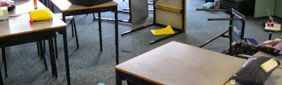classroom desks overturned on the floor