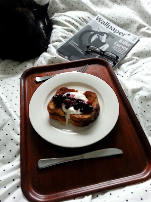 Cat curled up asleep on a bed next to a magazine and a tray holding a plate of french toast, yoghurt and berries.