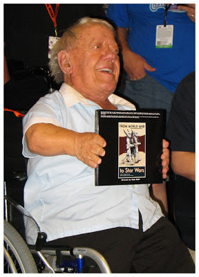 Kenny Baker holding From World War to Star Wars artwork
