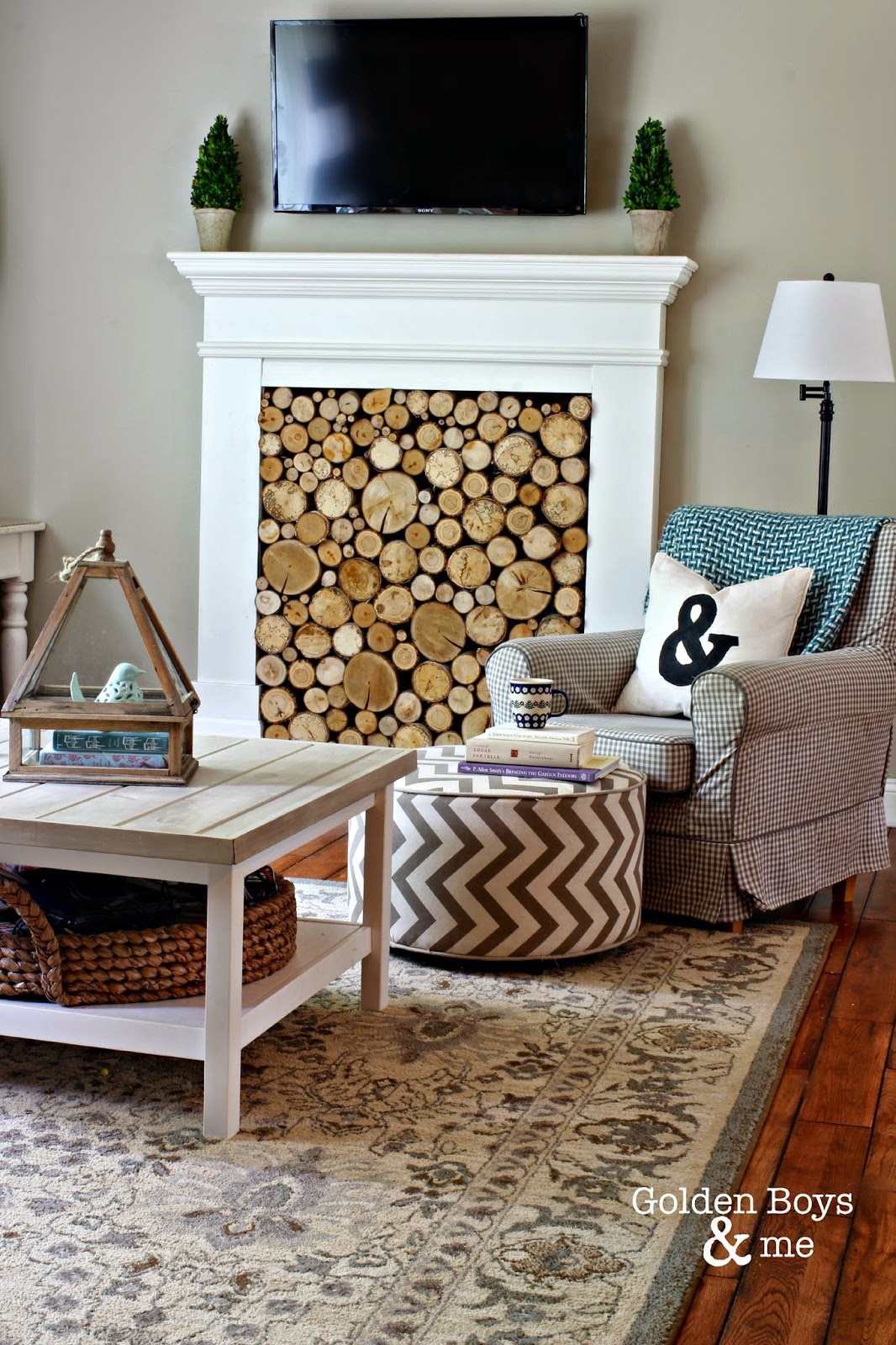 Faux fireplace with stacked wood and Ikea Jennylund chair with Ikea hack coffee table-www.goldenboyandme.com