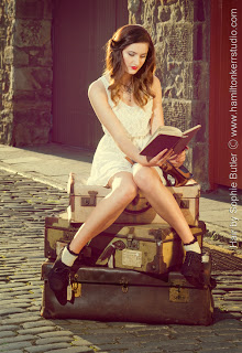 Model reading a book in an old fashioned street. Hamilton Kerr Studio. Sophie Butler Hair