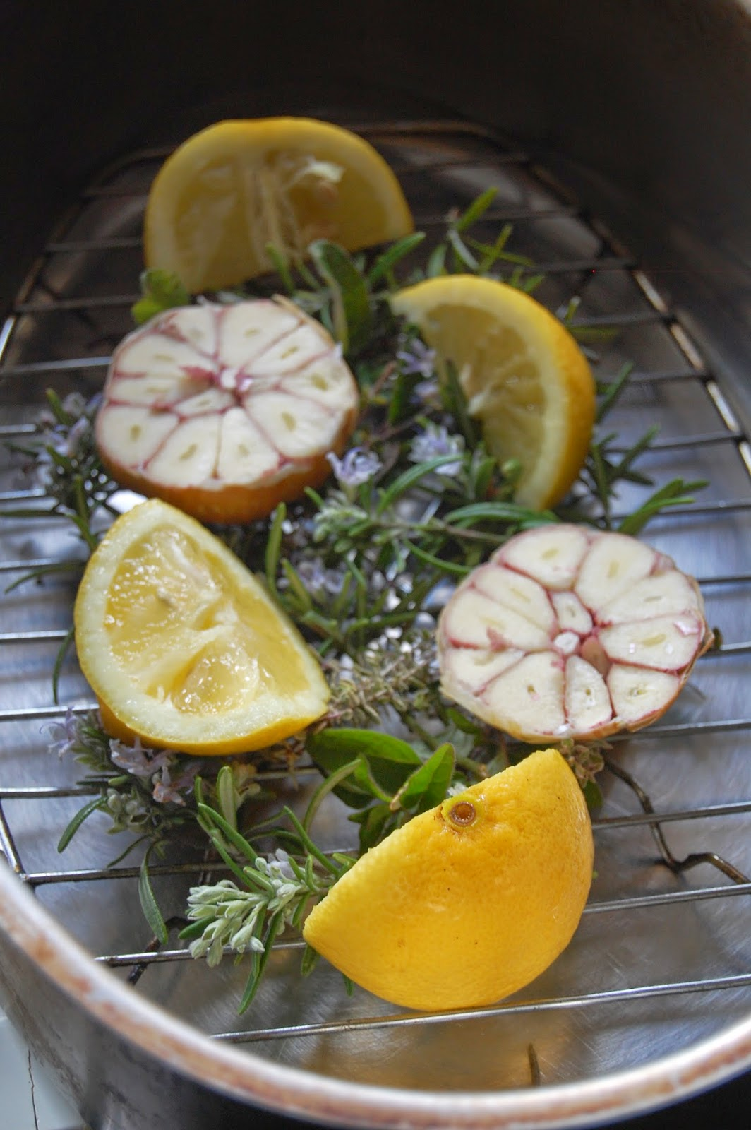 Place lemons, garlic and herbs in roasting tin