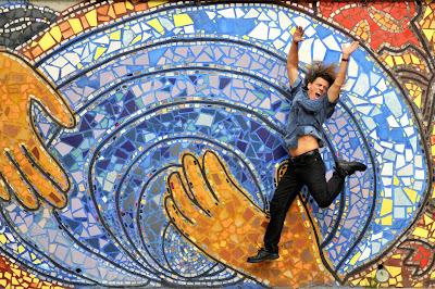 Foto hombre saltando frente a mural