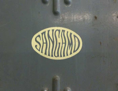 Wavy Sangamo lettering on a metal door