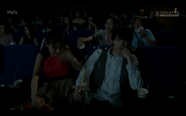 Matsumoto tries to hold Naoki's hand but Kotoko hits her with some airborne popcorn.