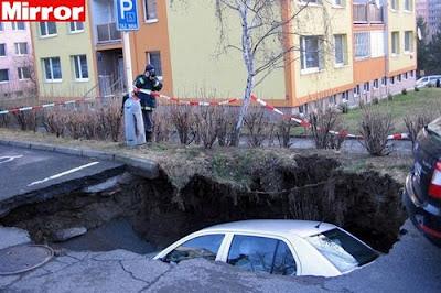 Asfalto engole carro estacionado em rua