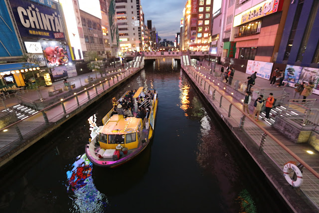 Boat ride along the canal at the popular tourist attraction of Dotonbori in Osaka downtown, Japan