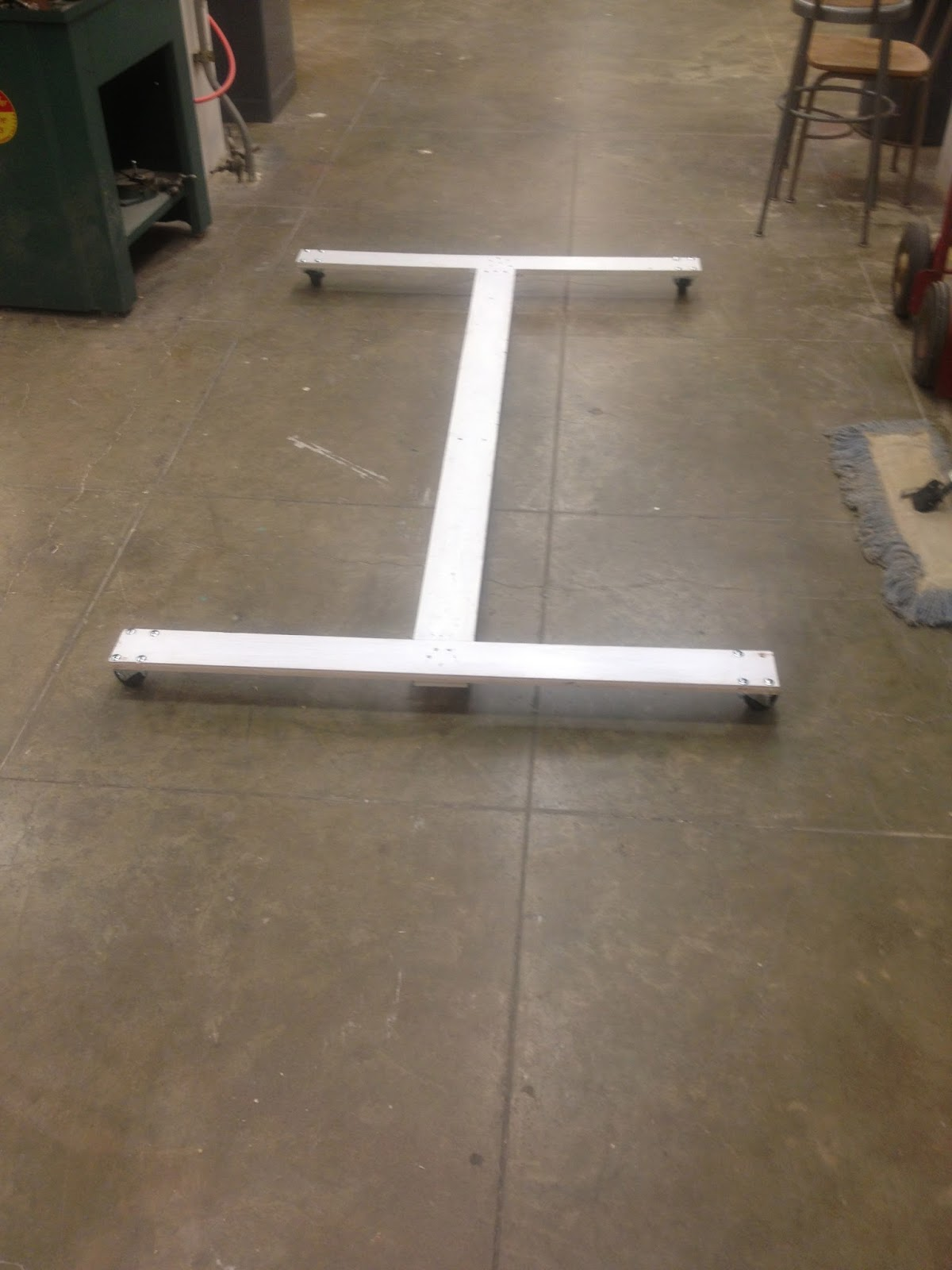 Three long wooden pieces are placed together in an I shape to after being painted. The pieces are put back together in order to reassemble them.