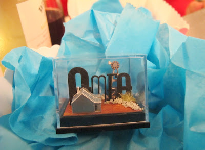 A small display box containing the letters 'AMEA', and a tiny cottage and windmill, displayed on some scrunched-up tissue paper.