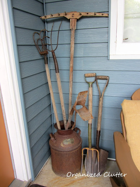 Vintage garden & farm tools in a rusty milk can