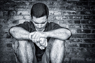 A depressed man sitting against a wall.