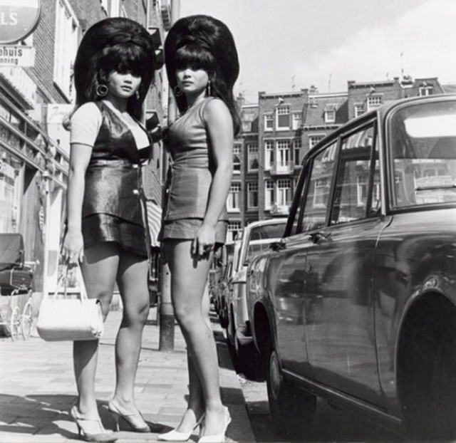 Two asian women sporting bee hives in Amsterdam during the 1960s