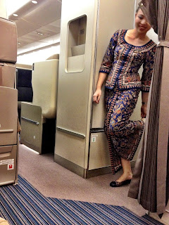 singapore airlines stuardess in economy during flight to tokyo