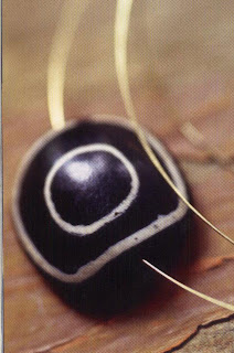 Dzi or magic eye. This very special agate is cut in successive layers that reveal white lines against a dark background. Collectors compete with each other for these Stone, especially in Asia, where their protective virtues are highly valued. If the Bone is pierced, it can be threaded with gold cord to snake a ring or necklace.