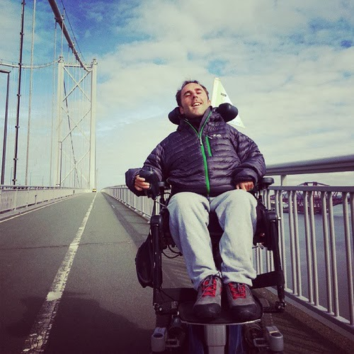 Man in electric wheelchair crossing a very long suspension bridge
