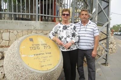 יגאל ודינה מצטלמים ליד השלט של שכונת בית מעון