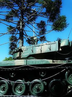 Tanque de guerra na Praça Central de São Marcos. Tanque em primeiro plano com araucária ao fundo.