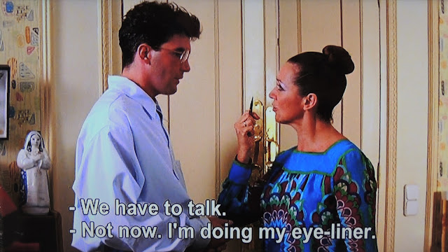 Lucia talking to Carlos with eyeliner in hand
