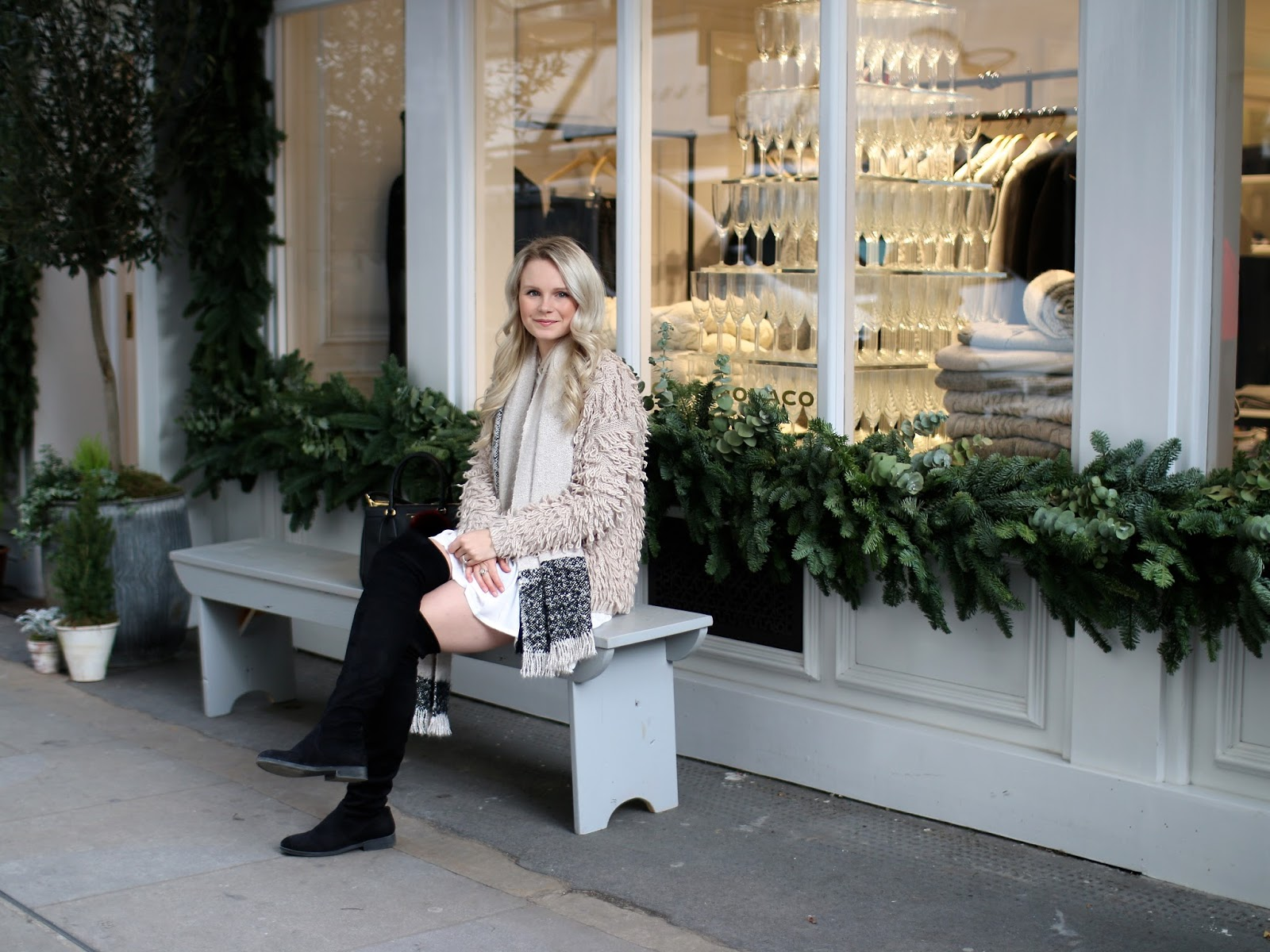 a blonde women sitting on a bench in front of club Monaco near seven dials in Covent Garden