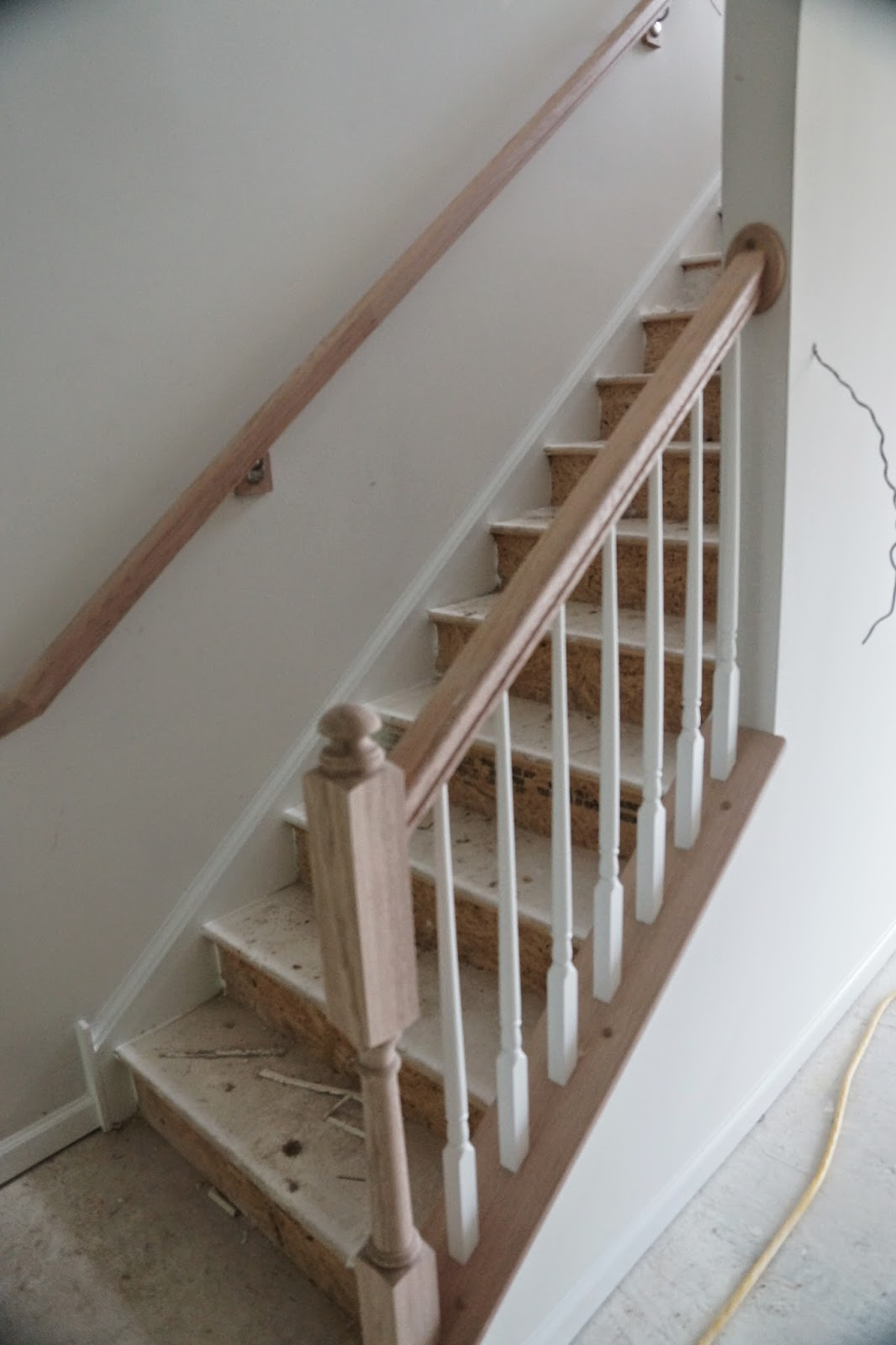 Picture of the unfinished banister on the bottom of the stairs as viewed from family room