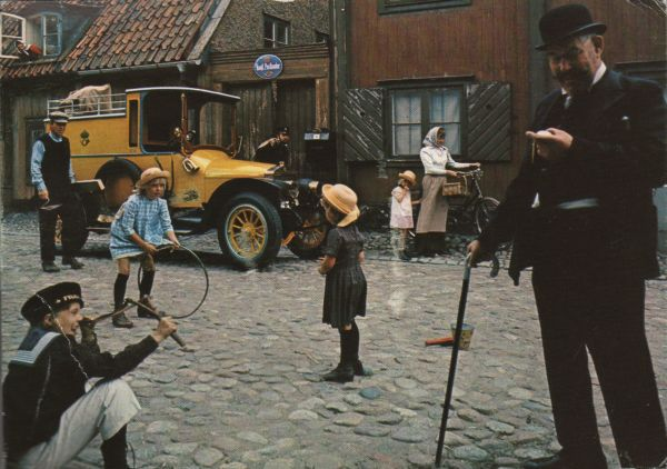 street scene from 1920 with yellow postal van