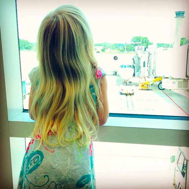 Blonde female child looking out airport window at airplane