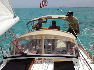 Nan, me and Aldo sailing Whispering Jesse, with Isla Mujeres in the background