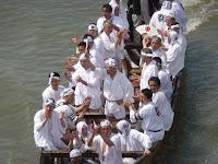 氏子の神輿担ぎ手たちはモーター付きの和船
