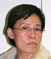 Headshot of a grim-expressioned middle-aged Korean woman wearing wire-rim glasses