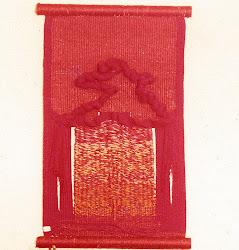Tecelagem de tear manual de pregos, em sisal vermelho e laranja, com volumetria em lã, e aberturas