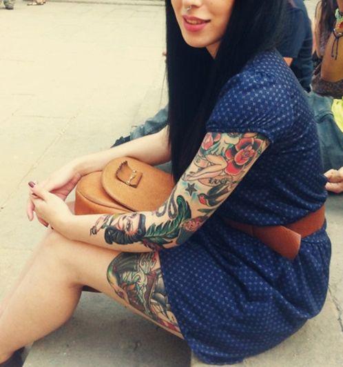 chica con tatuajes tradicionales sentada en la calle