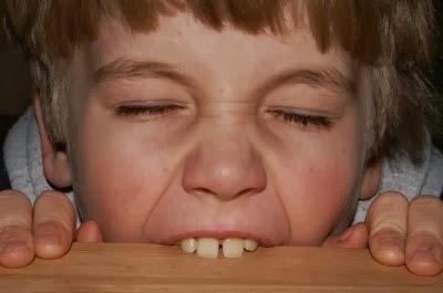 Kind beißt in einen Tisch