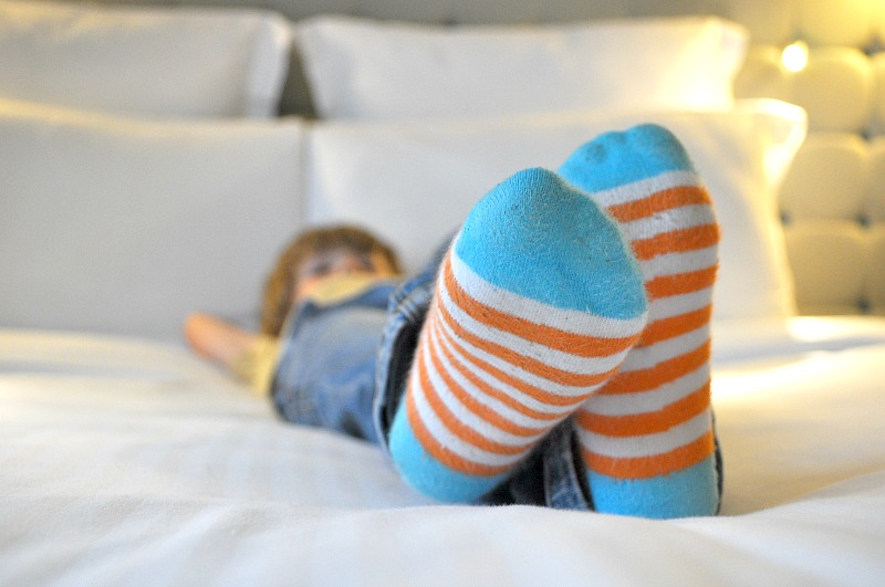 Child relaxing on bed with socks