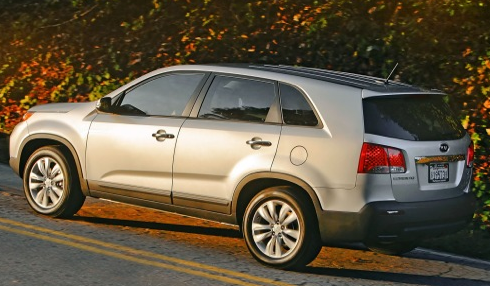 Rear 3/4 view of parked 2013 Kia Sorento on uphill street