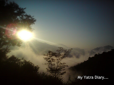 Sun peeping out from behind the cloud cover just before sunset in the Garhwal Himalayas