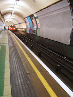 Image of the underground train tracks and tunnel with a train in sight