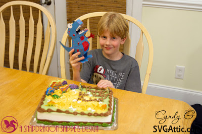 Young boy holding 3d paper dinosaur