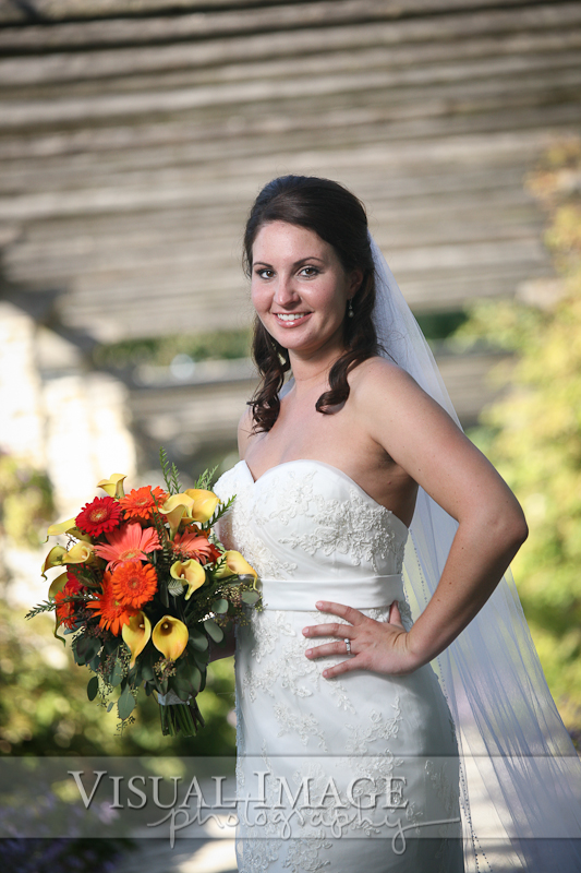 Portrait of bride with bouquet underneath arbor in Frame Park