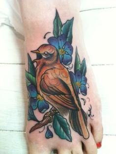 Kolorowy tatuaż ptaka na stopie