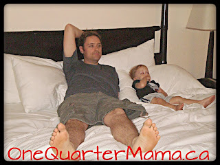 Dada and Little Man lying on hotel room bed