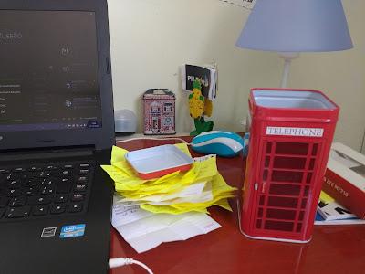 Uma mesa com um notebook, um abajur, alguns blocos de notas e no meio da foto há uma pequena pilha de bilhetinhos abertos e um pote retangular com o desenho de uma cabine telefônica londrina