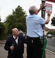 Alan Plant helping Brian Cox put up a sign