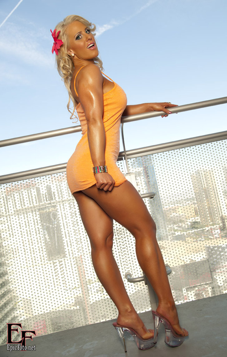Megan Avalon Posing Her Tan Legs In An Orange Dress And Heels