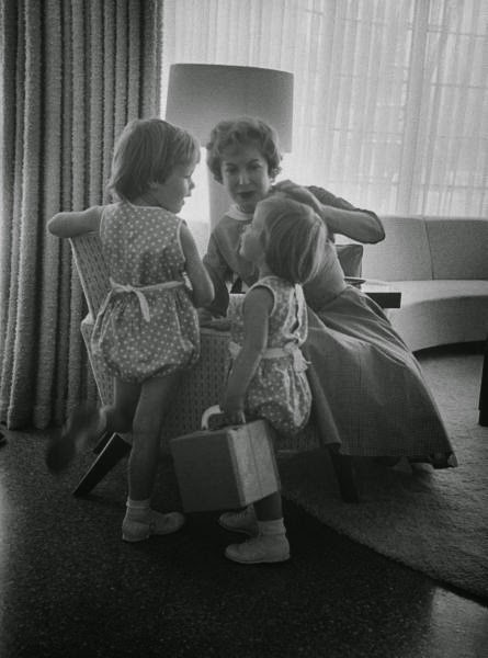 Gracie Allen twists a curl into place on Lissa before joining a card game.