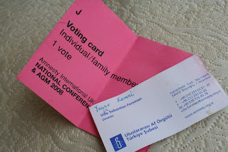 Amnesty International business card and AGM voting card.