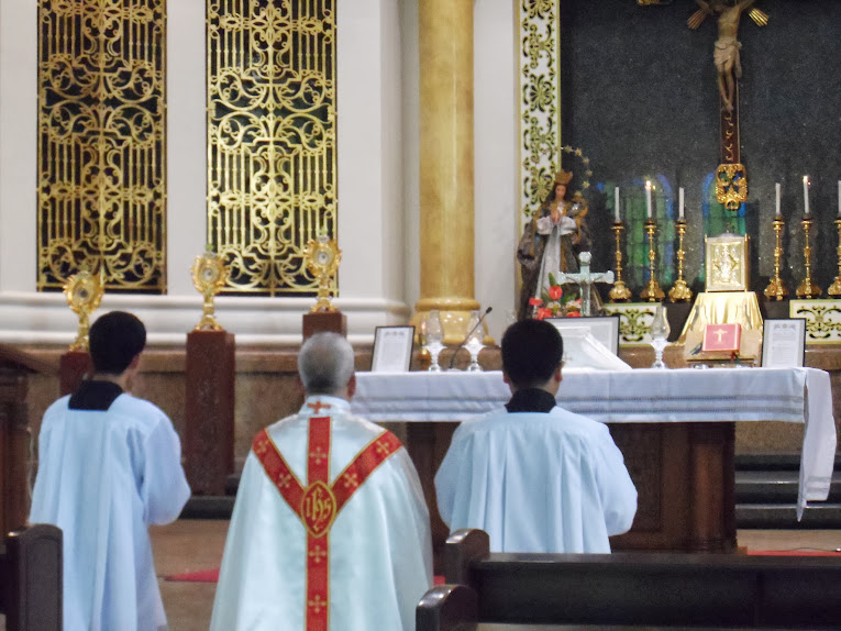Priest kneeling before the altar together with two servers
