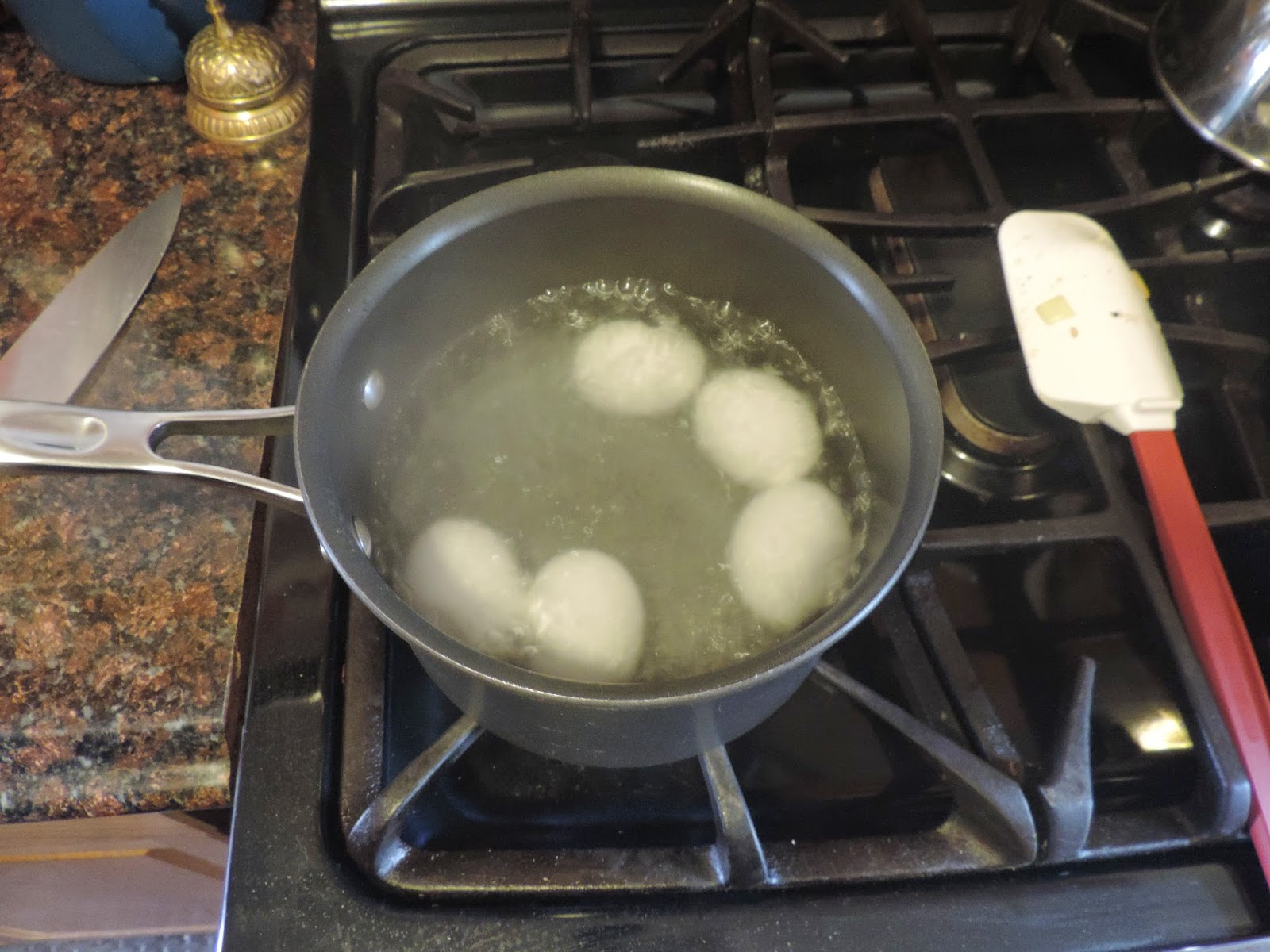 The water with the eggs in it being brought to a boil.
