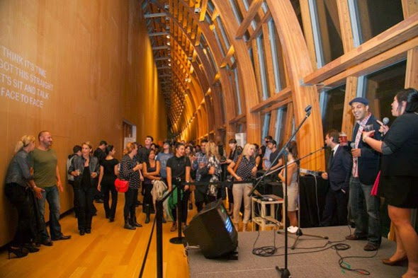 A group of people listen to a musical performance in the Galleria Italia at the Art Gallery of Ontario.